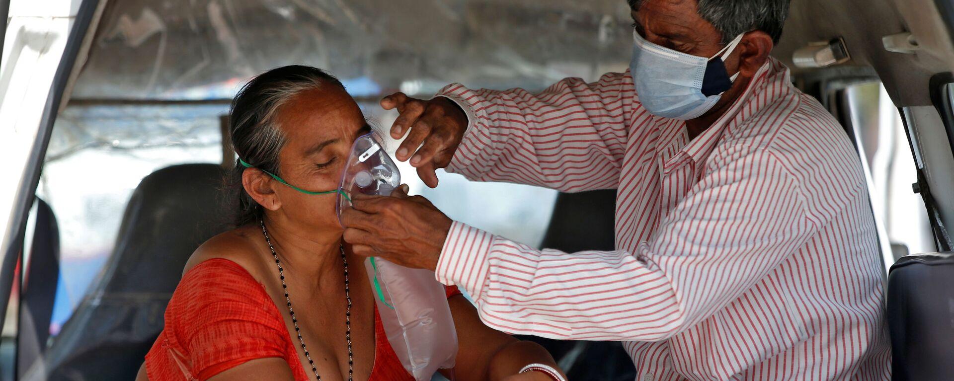 Muž upravuje kyslíkovou masku své ženě během čekání v autě na přijetí do nemocnice s covidem-19 k léčení, Indie - Sputnik Česká republika, 1920, 09.05.2021