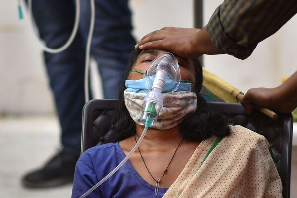 Žena trpící dýchacími potížemi dostává bezplatnou kyslíkovou podporu v sikhském chrámu v Dillí - Sputnik Česká republika
