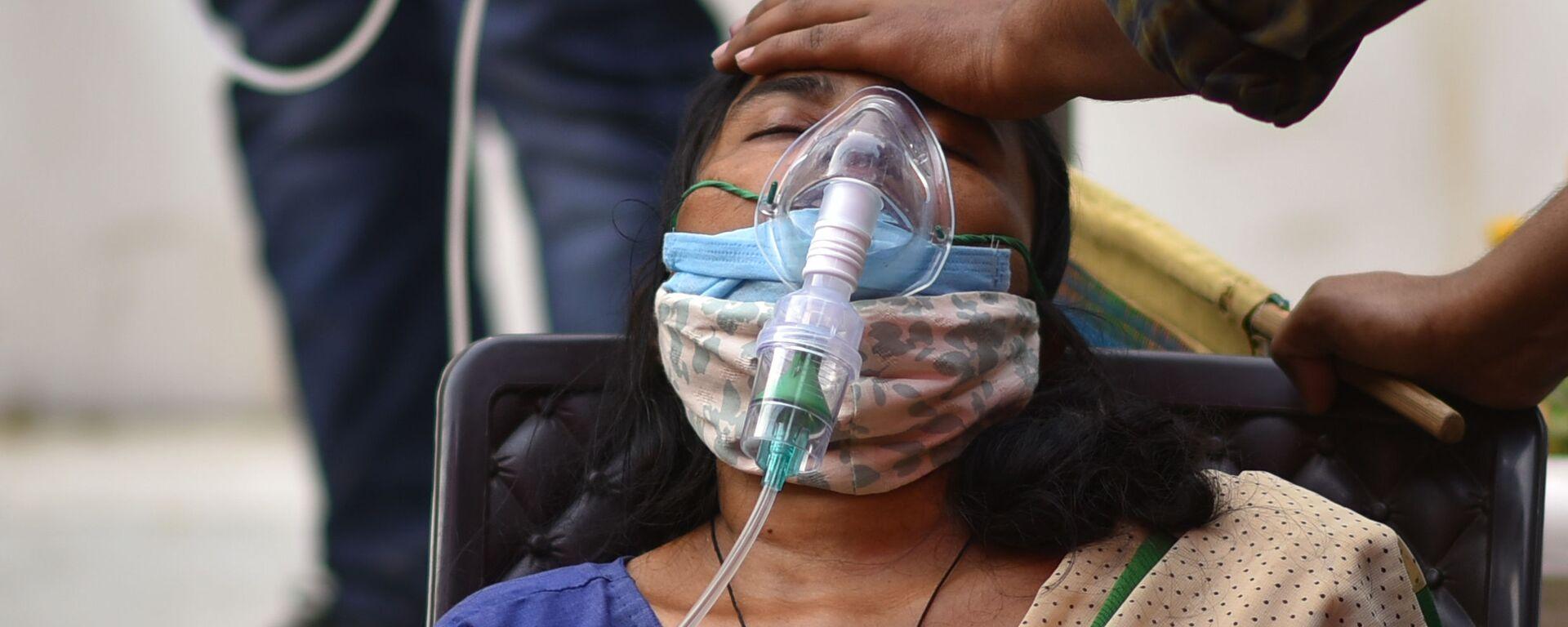Žena trpící dýchacími potížemi dostává bezplatnou kyslíkovou podporu v sikhském chrámu v Dillí - Sputnik Česká republika, 1920, 28.07.2021