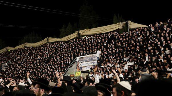 Еврейские верующие поют и танцуют, стоя на трибуне на мероприятии Лаг ба-Омер, Израиль - Sputnik Česká republika