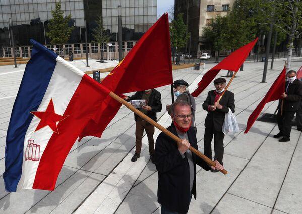 Muž drží starou jugoslávskou vlajku s komunistickou pěticípou hvězdou během májové demonstrace na Mezinárodní den pracujících v Bělehradě v Srbsku - Sputnik Česká republika