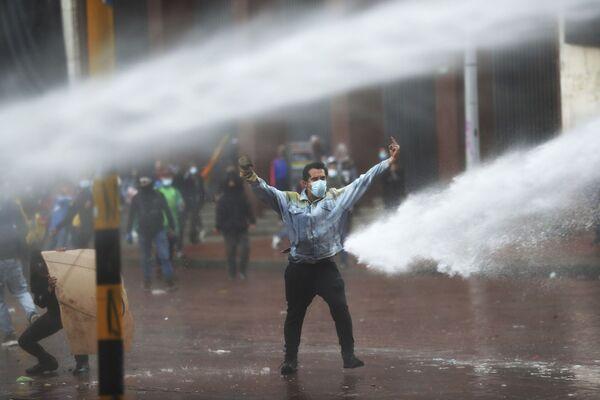 Účastník protestů během použití vodních děl ze strany policie. 5. května 2021. - Sputnik Česká republika