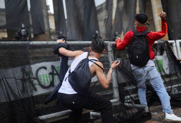 Demonstranti se chystají házet kameny během protestu proti chudobě a policejní brutalitě. Bogotá, Kolumbie. - Sputnik Česká republika