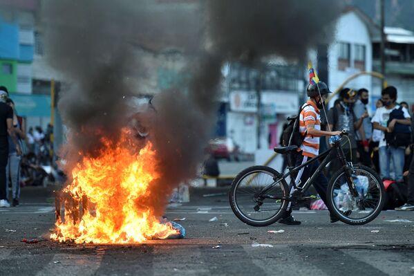 Demonstrant s kolem prochází mimo hořících barikád. Cali, Kolumbie. - Sputnik Česká republika
