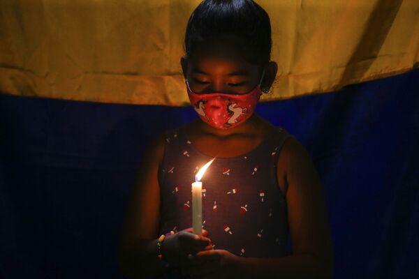 Kolumbijská dívka žijící v Panamě drží svíčku na podporu demonstrantů protestujících proti vládě. - Sputnik Česká republika