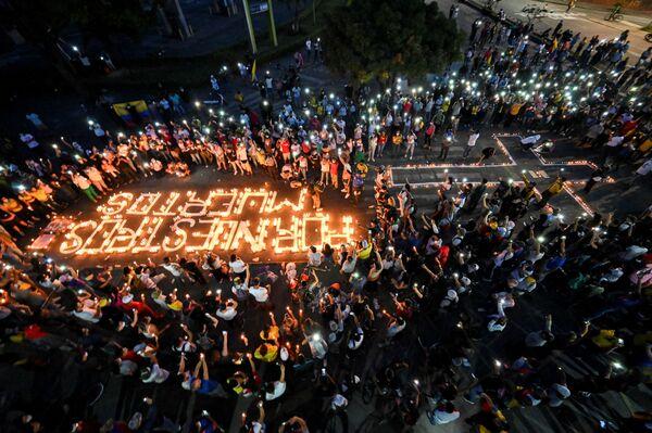 """Lidé se shromáždili kolem svíček a nápisu na chodníku """"za naše mrtvé"""" během noční hlídky v Cali, Kolumbie. - Sputnik Česká republika"""