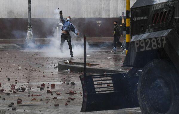 Protestující hází kameny na policejní vozidlo. Bogotá, Kolumbie. - Sputnik Česká republika