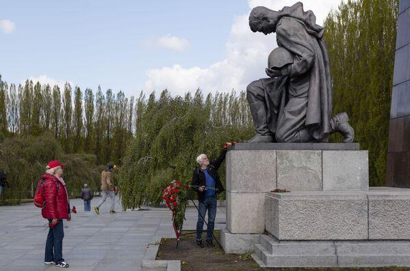 Muž pokládá květiny k soše sovětského vojáka. Berlín, Německo. - Sputnik Česká republika