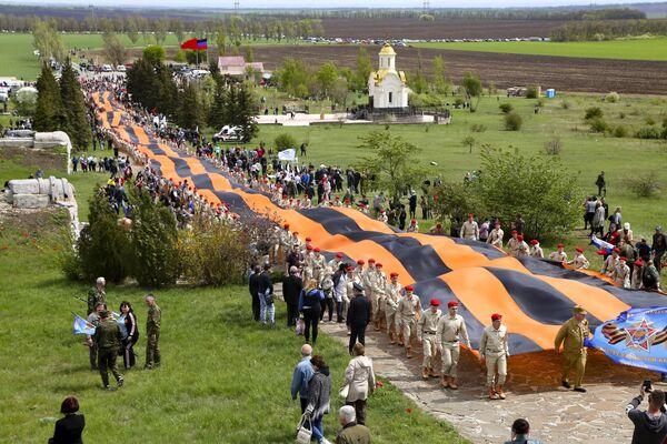Aktivisté nesou 300 metrů dlouhou stuhu v rámci oslav Dne vítězství poblíž Doněcka. - Sputnik Česká republika