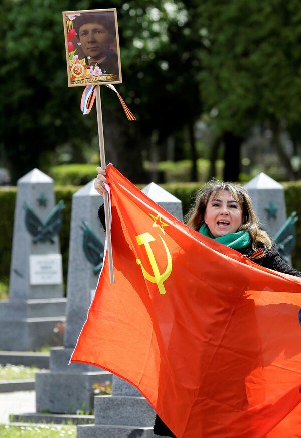Žena drží vlajku Sovětského svazu. Olšanské hřbitovy, Praha. - Sputnik Česká republika