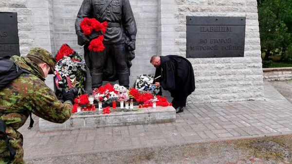 Kaplan vojenských sil Estonska pokládá věnec k památníku padlých vojáků. Tallin, Estonsko. - Sputnik Česká republika