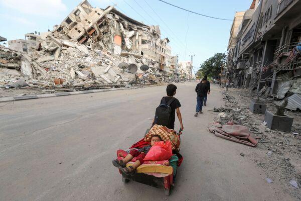 Palestinský chlapec táhne vozík s svým bratem a věcmi. - Sputnik Česká republika