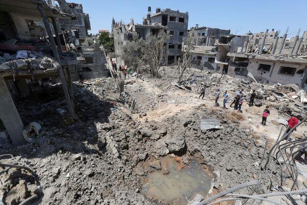 Palestinci vedle svých domů zničených v důsledku izraelského leteckého a dělostřeleckého útoku. - Sputnik Česká republika