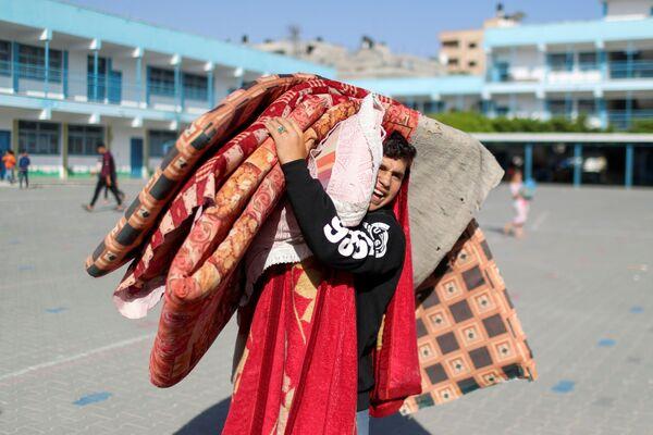 Palestinský mladík, který uprchl ze svého domova kvůli izraelským útokům, nese věci do svého nového útočiště – do školy. - Sputnik Česká republika