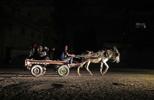 Palestinské rodiny v temné ulici po evakuaci ze svých domů na východě Gazy. - Sputnik Česká republika