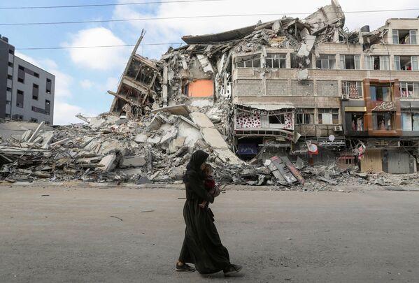 Palestinská žena s dítětem v rukou prchá ze svého domova.   - Sputnik Česká republika