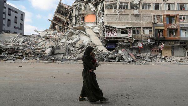 Палестинская женщина с сыном бежит из дома во время израильских воздушных и артиллерийских ударов - Sputnik Česká republika