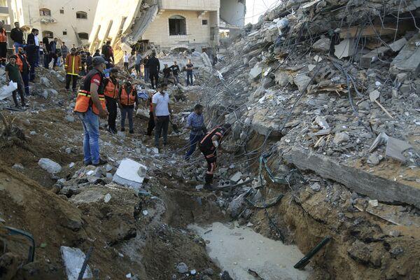 Palestinští záchranáři prohledávají trosky zříceného domu ve snaze najít věci a doklady rodiny al-Tanani. - Sputnik Česká republika