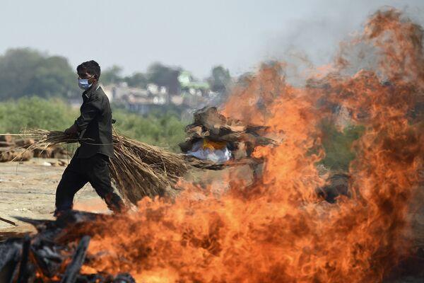 Dělník jde okolo planoucí pohřební hranice s lidmi, kteří zemřeli v důsledku koronaviru. Kremační místo v Allahabadu 8. května, 2021, kdy Indie poprvé zaznamenala více než 4 000 úmrtí na covid-19 za den. - Sputnik Česká republika