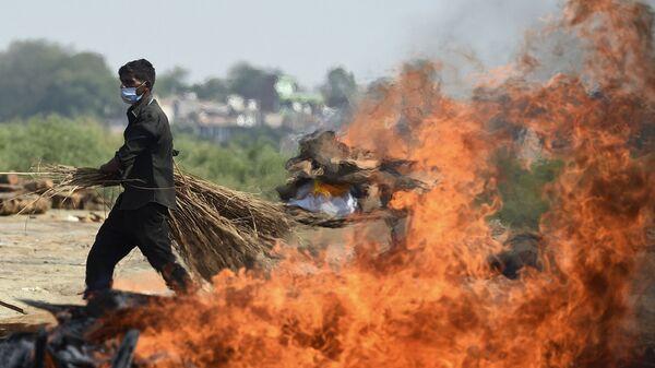 Рабочий проходит мимо горящего погребального костра человека, умершего из-за коронавируса Covid-19, Индия  - Sputnik Česká republika