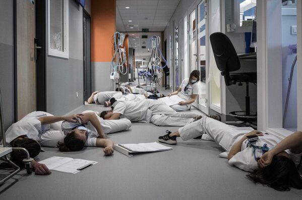 Zdravotnický personál leží na podlaze v nemocnici během demonstrace v Mezinárodní den ošetřovatelství a péče v nemocnici Mont Legia v Liege, Belgie. - Sputnik Česká republika