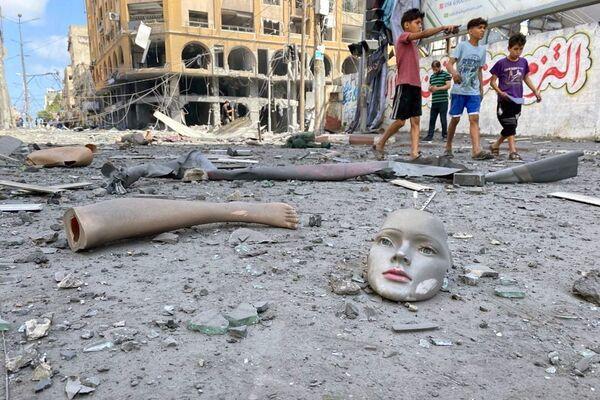 Části rozbité figuríny leží na zemi poblíž budovy, která byla zasažena izraelskými leteckými údery ve městě Gaza. - Sputnik Česká republika