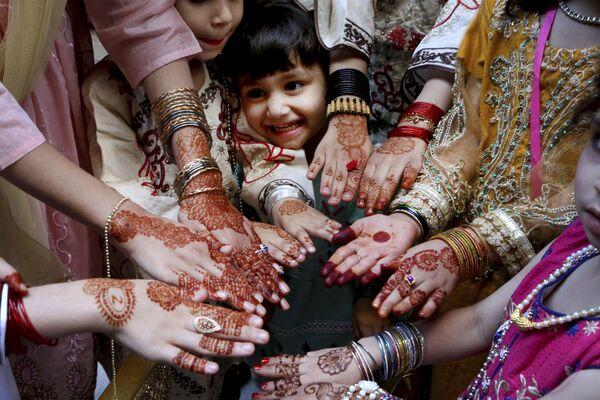 Muslimské dívky ukazují své ruce pomalované tradiční hennou na oslavu svátku Eid al-Fitr v Péšaváru, Pákistán. - Sputnik Česká republika