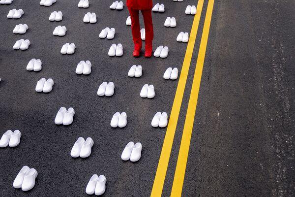 Žena v uniformě zdravotní sestry stojí obklopená bílými boty poblíž Bílého domu ve Washingtonu, aby reprezentovala 402 sester, které zemřely kvůli covidu-19. - Sputnik Česká republika