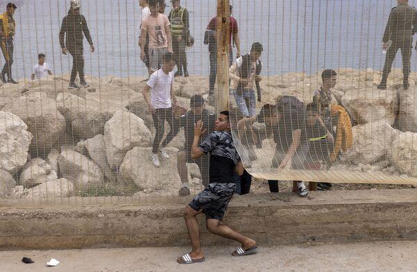 Maročtí migranti po pokusu překročit hranici mezi Marokem a španělskou exklávou Ceuta - Sputnik Česká republika
