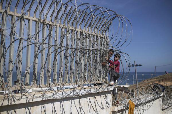 Migranti přelezli plot na hranici Maroka a Španělska poblíž španělské exklávy Ceuta - Sputnik Česká republika