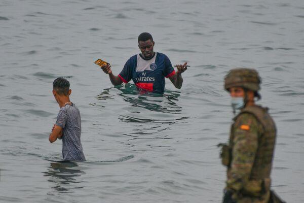Španělský voják stojí na stráži, když se migranti dostávají do španělské exklávy Ceuta - Sputnik Česká republika