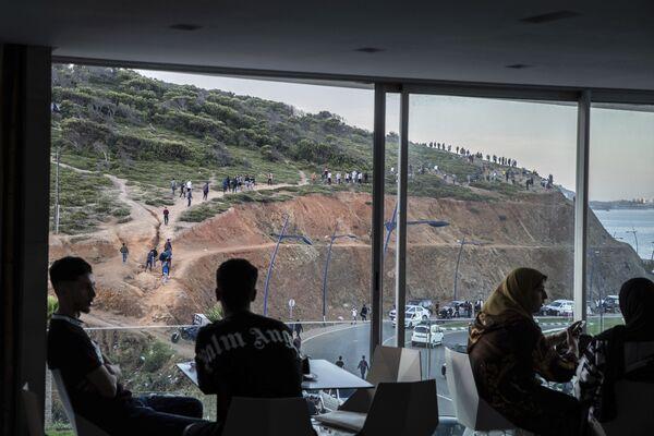 Lidé sedí v restauraci s výhledem na les, kde jsou vidět migranti mířící do španělské exklávy Ceuta - Sputnik Česká republika