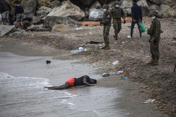 Muž leží na zemi, když španělská armáda uzavřela území na marocko-španělské hranici - Sputnik Česká republika
