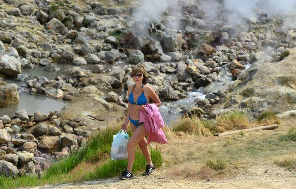 Žena kráčí po stezce v Dolině gejzírů na jednom ze sklonů vulkánu Mutnovskij.  - Sputnik Česká republika