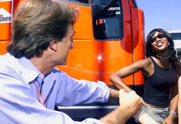 Britská topmodelka Naomi Campbell pózuje manažerovi týmu Ferrari na velké ceně Maďarska Formule 1 na závodním okruhu Hungaroring v roce 2000. - Sputnik Česká republika