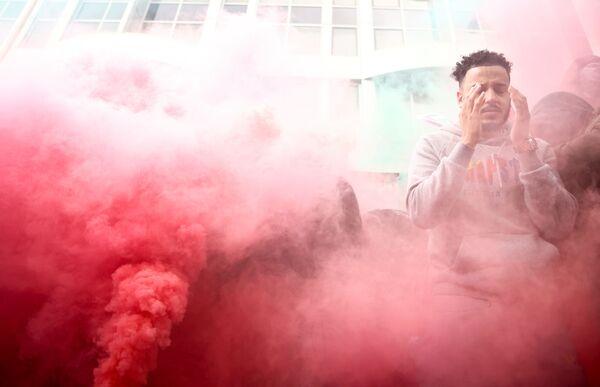 Reakce pro-palestinského demonstranta stojícího v dýmu během protestu v Londýně - Sputnik Česká republika