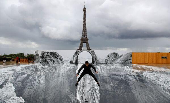 Muž pózuje na obřím díle francouzského umělce JR, instalovaném na náměstí Trocadero před Eiffelovou věží v Paříži - Sputnik Česká republika