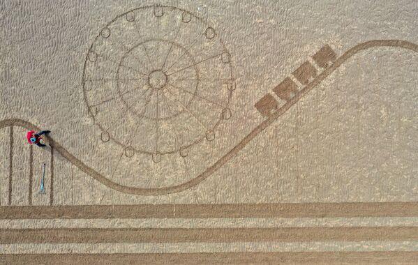 """Na leteckém snímku je písková malba zobrazující legendární věž, molo a atrakce Blackpoolu v severozápadní Anglii, namalovaná na pláži umělci z písku """"Písek ve vašem oku"""" jako znamení znovuotevření města po uvolnění omezení pro vstup do Anglie - Sputnik Česká republika"""