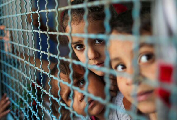 Palestinské děti, vyhnané ze svých domovů izraelským leteckým a dělostřeleckým útokem, které se dívají přes okna školy OSN, ve které se ukrývají. Gaza - Sputnik Česká republika