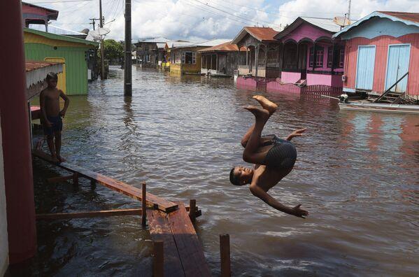 Chlapec skáče do vody v zaplavené ulici v Anamě v Brazílii - Sputnik Česká republika