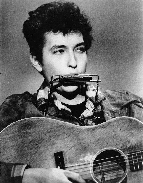 Bob Dylan hraje na foukací harmoniku a akustickou kytaru v březnu 1963 v jednom klubu - Sputnik Česká republika