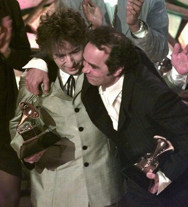 Bob Dylan (vlevo) a jeho producent Daniel Lanois se objímají poté, co zpěvák získal cenu za album roku na 40. ročníku udílení cen Grammy v New Yorku v roce 1998 - Sputnik Česká republika