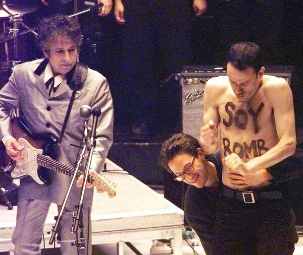 """Demonstranta s nápisem """"Sójová bomba"""" na těle odvádí z jevišti, když Bob Dylan zpívá píseň ze svého alba - Sputnik Česká republika"""