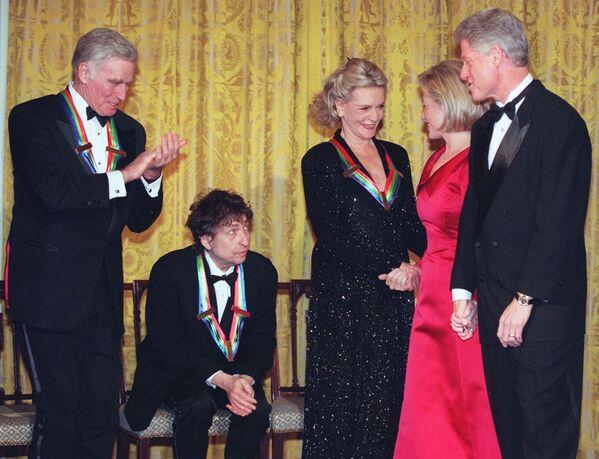 Americký prezident Bill Clinton (vpravo) a jeho manželka Hillary (druhá zprava) blahopřejí herečce Lauren Beckallové, herci Charltonovi Hestonovi (vlevo) a zpěvákovi Bobovi Dylanovi (druhý zleva) v Bílém domě ve Washingtonu - Sputnik Česká republika