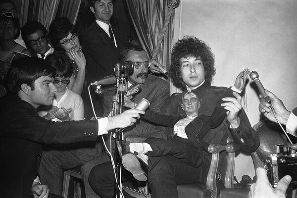 Americký folkový zpěvák Bob Dylan sedí s loutkou před novináři během tiskové konference v hotelu George V Hotel v Paříži, Francie, r. 1966 - Sputnik Česká republika