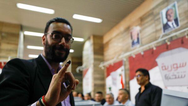 Мужчина с покрытым чернилами пальцем во время президентских выборов в Сирии - Sputnik Česká republika