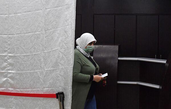 Žena volí v prezidentských volbách v Sýrii ve volební místnosti v Damašku  - Sputnik Česká republika