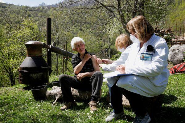 Muž dostává vakcínu proti koronaviru (covid-19) vedle kotlíku ve vesnici Ljevista v Černé Hoře - Sputnik Česká republika