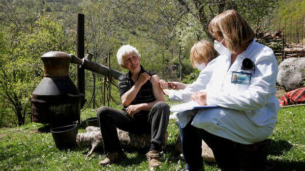 Мужчина получает вакцину от коронавируса (COVID-19) рядом с горшком бренди в деревне Левиста, Черногория - Sputnik Česká republika