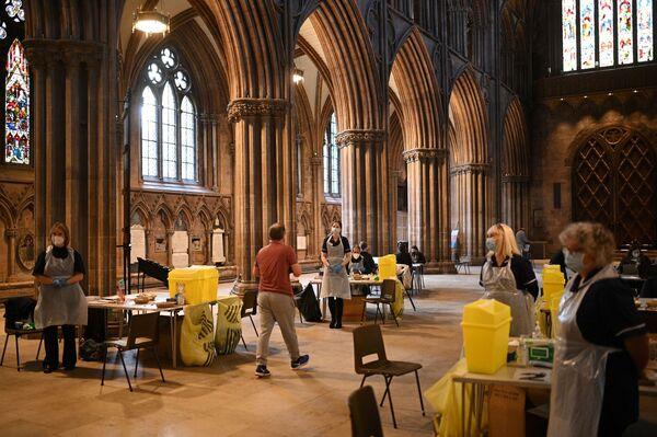Lidé dostávají dávku vakcíny Oxford / AstraZeneca v Lichfieldské katedrále v Anglii - Sputnik Česká republika